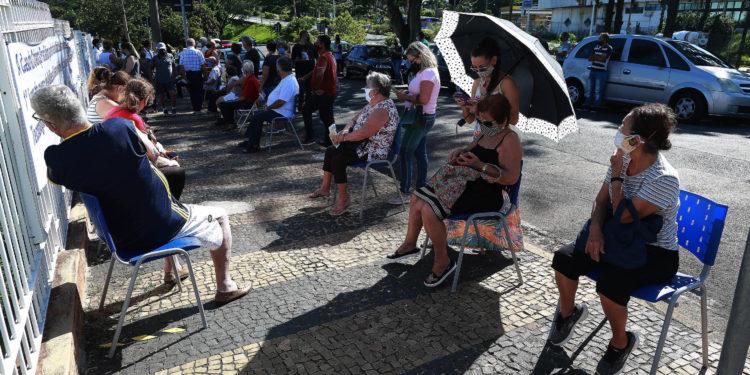 Idosos aguardam sentados na calçada para tomarem a vacina, no posto montado na Casa da Criança Paralítica.  Foto: Leandro Ferreira/Hora Campinas
