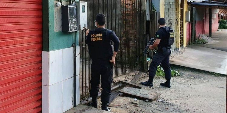 Policiais federais diante da casa de um suepeito: nome da operação, Catraia, é uma referência às embarcações, muito comuns na região do Oiapoque, usadas no transporte de pessoas e mercadorias para a Guiana Francesa e Suriname Foto: Dvulgação