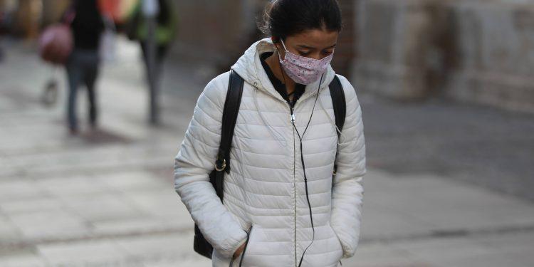 Jovem caminha protegida do frio e da Covid-19 no Centro de Campinas: rejuvenecimento da pandemia mudou a dinâmica no atendimento nos PSs e hospitais Foto: Leandro Ferreira/Hora Campinas