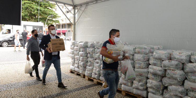 Voluntários coletam produtos alimentícios em campanha feita pela Associação de Revendedores de Veículos no Largo do Rosário. Foto: Divulgação