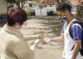 Funcionário higieniza mão de estudante na porta da escola em Jaguariúna: retomada Foto: Ivair de Oliveira/Divulgação